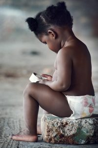adorable little black african baby playing with trash in rural poverty area