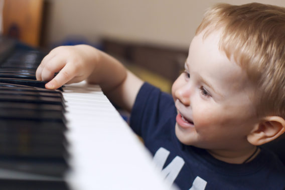 Small boy enjoys playing electric piano (synthesizer) for the first time