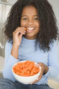 Girl eating bowl of carrots